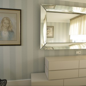 Na przeciwko łóżka znajduje się lustro w ozdobnej,połyskującej ramie. Klasyczną sypialnię uzupełniają stoliki nocne oraz komoda o nowoczesnym, geometrycznym kształcie. Proj.Małgorzata Borzyszkowska. Fot.Bartosz Jarosz.