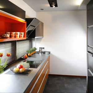 W długiej, wąskiej kuchni zamontowane tuż nad oknami szafki zostały całkowicie otwarte. Dzięki temu udało się optycznie powiększyć niedużą przestrzeń kuchni. Projekt Anna Gruner. Fot. Bartosz Jarosz.