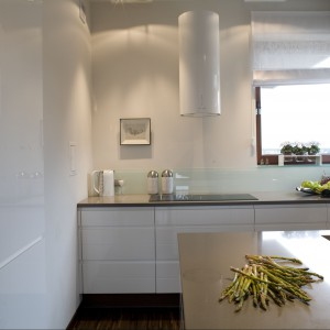 Aranżacyjną czystość projektu kuchni podkreśla stylowy biały okap w kształcie tuby zamontowany tuż przy oknie. Projekt Małgorzata Szajbel-Żukowska. Fot. Marcin Onyfryjuk.