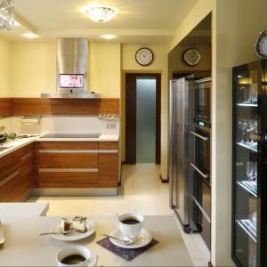 Ciepło eleganckiej kuchni podkreśla zamontowany tuż nad blatem fornir o pięknym, miodowym wybarwieniu drewna. Razem z nowoczesnym okapem stanowi on jedyną, ale zupełnie wystarczająca dekorację ściany. Projekt Piotr Stanisz. Fot. Bartosz Jarosz.