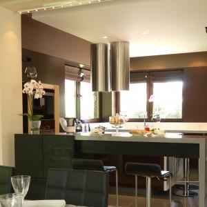 W dużej kuchni utrzymanej w ciepłych barwach całkowicie zrezygnowano z górnej zabudowy. Pomalowane ciemnobrązową farbą ściany kuchni podkreślają jej salonowy charakter. Projekt Tomasz Tubisz. Fot. Przemysław Andruk.