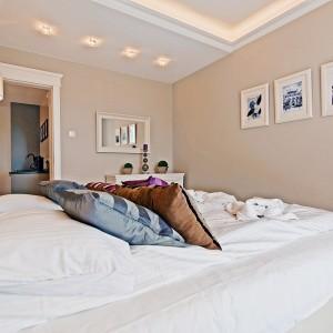 W sypialni swoje miejsce znalazła stylizowana, wąska bieliźniarka, stoliki nocne i lustro w białej ramie. Fot. Sun&Snow.