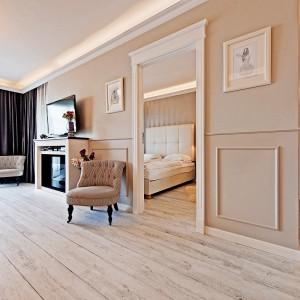 Ściany wyłożono boazerią w stylu prowansalskim oraz tłoczoną, połyskującą tapetą z geometrycznym wzorem. Fot. Sun&Snow.