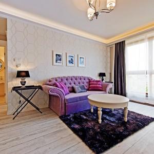 Głównymi akcentami kolorystycznymi stała się pikowana sofa w kolorze fioletowym oraz grubo tkane granatowe zasłony. Fot. Sun&Snow.