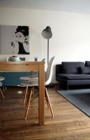 Projektowane wnętrze stanowi połączenie nowoczesności z domowym, przytulnym charakterem, zachowując przy tym klasę oraz styl całości zamierzenia. Dominującym kolorem stała się biel, ocieplona naturalną, drewnianą podłogą o dość wyraźnym usłojeniu. Charakter wnętrza tworzą barwne akcenty o różnorodnych formach i funkcjach. Dzięki nim przestrzeń staje się ciekawsza i mniej monochromatyczna. Klimat wnętrza stanowi idealne tło dla nowoczesnych mebli oraz nietuzinkowej, industrialnej lampy stojącej, która stała się ulubionym elementem aranżacji Właścicieli.