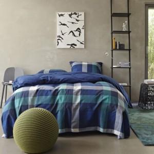 Kolorowe, wzorzyste tkaniny w sypialni doskonale komponują się z szarą, betonową ścianą. Na zdjęciu pościel Darwin od Essenza. Fot.Essenza.