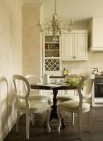 Elegancka kuchnia w bieli, urządzona ze smakiem i wyczuciem. Łączy ze sobą idealnie ozdobność i funkcjonalność. W szafkach każda pani domu pomieści to wszystko, co jest potrzebne. Dodatki natomiast, takie jak żyrandol czy zwiewne firany dodają klasy i elegancji.