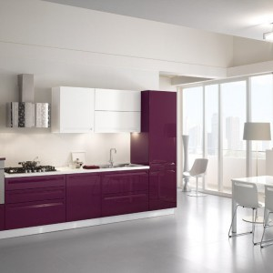 Meble z kolekcji Tropea Spar firmy Arreda. Idealne do niewielkiej kuchni – zabudowa zajmuje tylko jedną ścianę. Fioletowe fronty w połysku doskonale ożywiają jasne wnętrze i w ich otoczeniu jeszcze bardziej zyskują na intensywności.