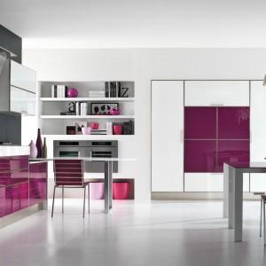 Meble z kolekcji Lucy od firmy Lube Cucine. Jasne wnętrze ożywia kolor dojrzałego bakłażanu, który zastosowano nie tylko na kuchennej zabudowie. Odnajdziemy go również na meblach w salonie oraz w dodatkach. Całość tworzy spójną, estetyczną strefę dzienną.