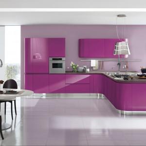 Meble z kolekcji Capri z oferty firmy Aerre Cucine. Fronty w intensywnym fioletowym kolorze nadają indywidualny i bardzo oryginalny charakter kuchni otwartej na salon. Zabudowa ma ładny, opływowy kształt.
