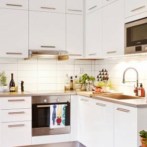 Prosta biała kuchnia z drewnianymi blatami. Fot. Stadshem.