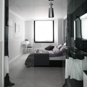 Granica między strefą sypialnianą a łazienkową wyznacza tafla szkła oraz czarno- białe zasłony. Proj.Magdalena Smyk. Fot. Bartosz Jarosz.