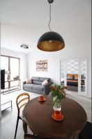 Minimalistyczny salon z częścią kuchenną. Dominującą biel ożywia  wprowadzenie brązowego i pomarańczowego, które pojawiają się w różnych, mniej lub bardziej drobnych elementach - krzesłach, świecach czy pięknym, drewnianym stole.  Ciekawy akcent stanowi również geometryczny wzór, wykorzystywany w różny sposób na ścianie, poduszkach czy grafice. Powtarzalność tych dwóch motywów - koloru oraz wzoru nadaje wnętrzu spójność, tworząc z dwóch części intrygującą całość.