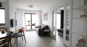 Minimalistyczny salon z częścią kuchenną. Dominującą biel ożywia wprowadzenie brązowego i pomarańczowego, które pojawiają się w różnych, mniej lub bardziej drobnych elementach - krzesłach, świecach czy pięknym, drewnianym stole.