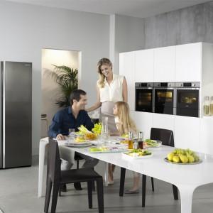 W tej kuchni widoczny jest sprzęt AGD marki Samsung. Duża lodówka typu Side by Side w kolorze stali i okap doskonale pasują do biało-szarej kuchni w nowoczesnym stylu. Nie gorzej prezentują się urządzenia w zabudowie. Fot. Samsung.