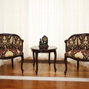 Między kuchnią a jadalnia znajduje się miejsce na chwilę odpoczynku. Drewniane krzesła mają ładne tapicerowane obicie z wyrazistym wzorem. Do kompletu dodano malutki stolik, również wykonany z drewna. Projekt: Magdalena Mirek-Roszkowska. Fot. Bartosz Jarosz. Stylizacja: Ewa Kozioł.