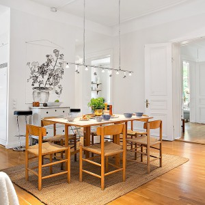 Nowoczesny klimat wprowadza oświetlenie nad stołem i grafika na ścianie. Fot. Alvhem Makleri.
