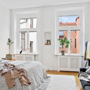 Sypialnia urządzona w bielach i szarościach. Fot. Alvhem Makleri.
