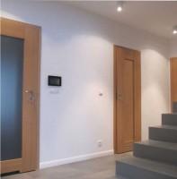 Strefa wypoczynkowa pokoju dziennego w domu jednorodzinnym jest obszerna i bardzo jasna.  Postawiono na prostotę i ekonomikę rozwiązań. Prosty czopuch kominka sąsiaduje z biblioteczką zbudowaną z półek Ikea Lack, pozioma kamienna półka wykonana jest z granitu szczotkowanego.  Proste i nowoczesne są też meble i dodatki. Podłoga z paneli laminowanych imitujących dębowe deski łączy się bezlistwowo z pasmem szarych kafli wzdłuż ściany kominkowej.  Oprawy oświetleniowe neutralnie zlewają się z tłem ścian i sufitu.