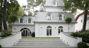 Zaprojektowana według secesyjnej koncepcji zieleń wokół domu przyciąga elegancją, przejawiającą się w wyszukanych formach elementów zdobnych otaczających stylowy dworek. Tu zieleń traw wraz z bielą budynku spajają się w
