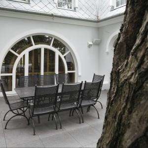 Duże, przeszklone drzwi w kształcie łuku prowadzą do jadalni - tej ogrodowej oczywiście. Piękne kute meble zachowują ich półokrągłą linię. Fot. Bartosz Jarosz.