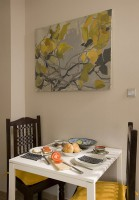 Kuchnia w kamienicy przy Łazienkach - niewielka, ale funkcjonalna. Szare fronty mebli dobrze komponują się z beżowymi ścianami - tak dobrana kolorystyka sprawia, że kuchnia wydaje się oazą spokoju. Stylowe dodatki pogłębiają ten efekt, a mały stolik i pięknie zdobione krzesła zapraszają do chwili odpoczynku.