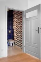Projekt toalety w odcieniach koloru niebieskiego. Ścianę zdobi tapeta w geometryczne wzory.