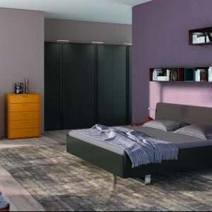 Jasny i ciemny fiolet dodaje sypialni elegancji. Na jego tle doskonale prezentują się drewniane meble. Na zdjeciu sypialnia z serii Aumera. Fot.Hulsta.