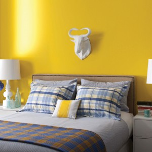 Ściana w intensywnym, żółtym kolorze wprowadzi do wnętrza sporą dawkę energii. Żółty dobrze łączy się z szarościami, bielą oraz czarnymi akcentami.Fot.Benjamin Moore.