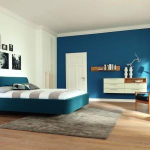 Użycie intensywnego koloru tylko na jednej ścianie to doskonały pomysł na wprowadzenie kolorystycznego akcentu do wnętrza. Niebieska ściana koresponduje z tapicerowanym łóżkiem. Fot.Hulsta.