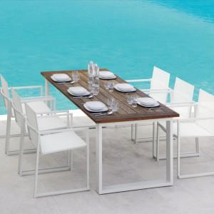 Stół ogrodowy Essence to ikona stylu marki Talenti. Jego podstawa wykonana została z aluminium, a blat z drewna teakowego. Doskonale prezentuje się z białymi krzesłami o prostej formie. Fot. Talenti.
