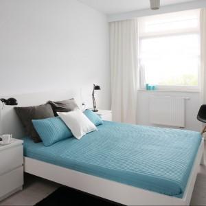 Białe ściany, łóżko, stoliki nocne, lampa – dużo bieli wprowadza do sypialni spokój, porządek. Biel jest czysta, neutralna, stanowi doskonałe tło dla barwnych dodatków. Wnętrze ożywiają kolorowe akcenty. Smaku dodają czarne lampki nocne, krzesło, dywanik. Fot. Bartosz Jarosz.