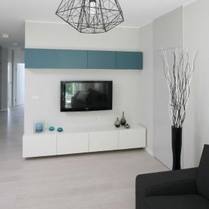 Meble na ścianie telewizyjnej dobrano z prostotą, a jednocześnie tak, by tworzyły całość stylistyczną i kolorystyczną z otwartą zabudową kuchenną. Pochodzą z oferty IKEA, a wykonano je z matowego MDF-u. Fot. Bartosz Jarosz.