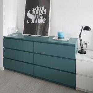 Turkusowa komoda z IKEA to kolejne nawiązanie do mebli znajdujących się w pozostałej części domu. Jej kolor harmonizuje z tkaninami i dekoracjami, dzięki czemu aranżacja ma spójny charakter. Fot. Bartosz Jarosz.
