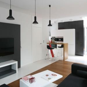 Czarno-białą kompozycję podkreśla stolik kawowy o ciekawej, asymetrycznej formie, do którego została doprojektowana szafka RTV. Neutralne barwy ociepla drewniana podłoga wpasowana w sposób przypominający ułożenie dywanu. Fot. Bartosz Jarosz.