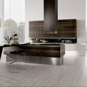 Meble z kolekcji Neos firmy Rational. Funkcjonalna, nowoczesna kuchnia ulokowana jest w otwartej strefie dziennej, chodź salon skryty jest za ścianką umieszczoną na środku pomieszczenia. Widok za całkowicie przeszkloną elewacją możemy obserwować siedząc przy stole.