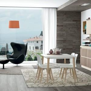 Meble z kolekcji Ank firmy Creo Kitchens. Ogromne okno pozwala cieszyć się widokiem zarówno w części wypoczynkowej, jak roboczej bo kuchnia znajduje się w otwartej strefie dziennej. Fronty mebli o fakturze drewna nadają wnętrzu ciepły, domowy klimat.