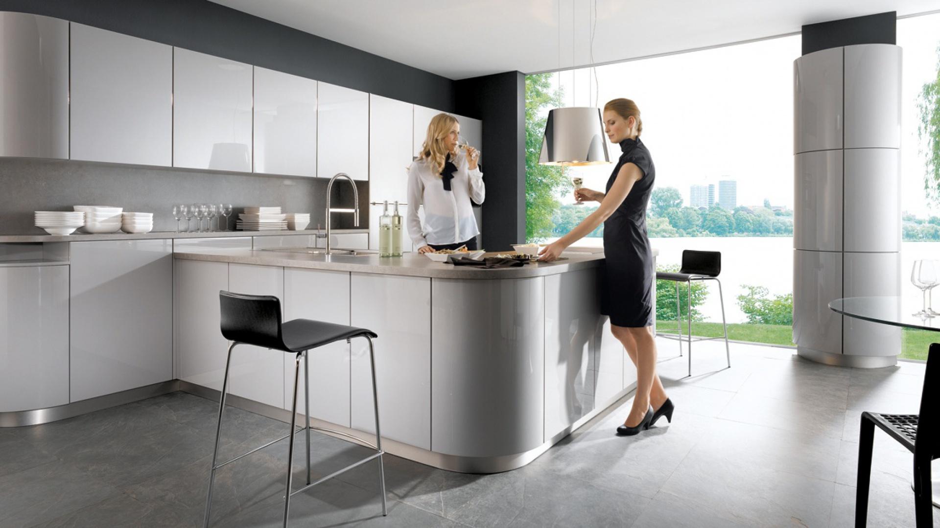Meble z kolekcji Gala L236 firmy Schüller. Nowoczesny charakter kuchni podkreślają szare fronty lakierowane na wysoki połysk i otwierane bezuchwytowo. Szare są również kamienne blaty. Ogromne przeszklenia pozwalają cieszyć się widokiem za oknem z każdego miejsca w kuchni.