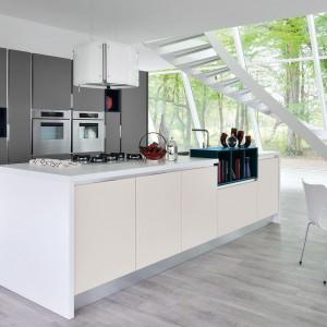 Meble z kolekcji Essenza z oferty firmy Lube Cucine. Przeszklona elewacja doskonale doświetla otwarte wnętrze kuchni i zapewnia piękny widok za oknem – inny o każdej porze roku. Biało-szara kolorystyka i fronty otwierane bezuchwytowo nadają jej nowoczesny charakter.