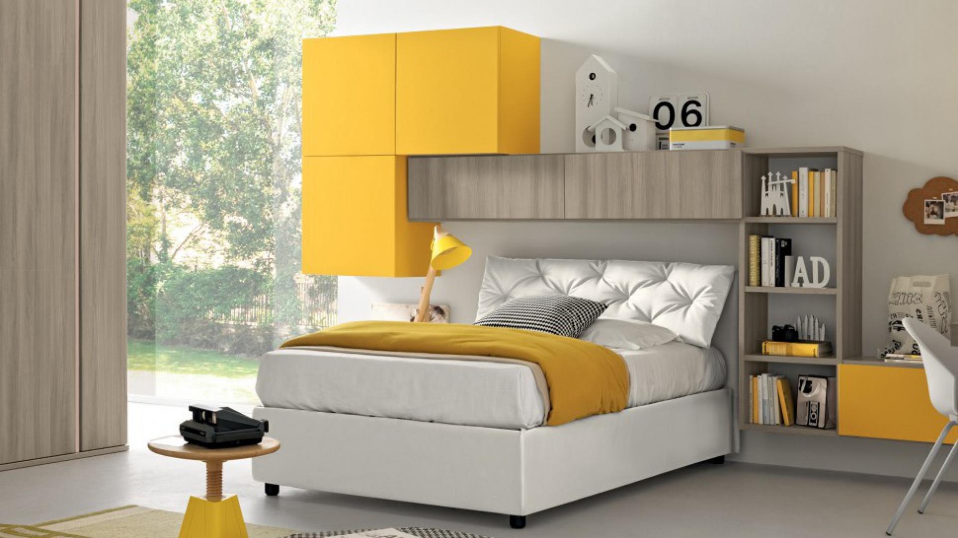 Z żółtymi frontami meblościanki koresponduje słoneczny koc, lampka nocna i niewielki stolik. Fot. Colombini Casa.