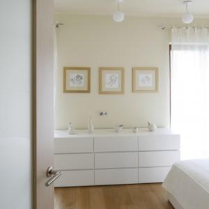 Białe meble w połączeniu z drewnianą podłogą oraz delikatnym odcieniem ścian tworzą łagodną kompozycję. Proj. Małgorzata Borzyszkowska. Fot.Bartosz Jarosz.