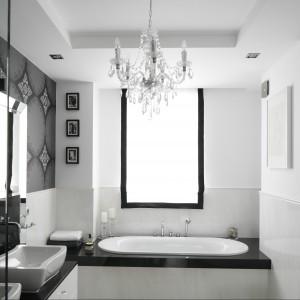 Biała, zaaranżowana w stylu glamour łazienka połączona została z sypialnią. Stąd wybór tak łagodnego, czystego i sprzyjającego wypoczynkowi koloru jakim jest biel. Aby jednak aranżowana przestrzeń nie stała się zbyt nudna ożywiła ją czerń. Barwa bardzo elegancka, która dodatkowo nie przytłoczyła licznie obecnych w stylizacji elementów neobarokowych. Projekt Magdalena Smyk. Fot. Bartosz Jarosz.