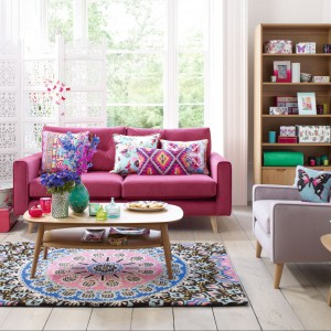 Sofa uzupełniona o dodatki w różowym kolorze to recepta na subtelną aranżacje. Fot. Debenhams.
