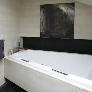 """Asymetryczna wanna do zabudowy podkreśla skosy łazienki, które dzięki """"wysunięciu"""" ścian nad czarnymi wnękami zostały widocznie zniwelowane. Projekt Piotr Stanisz. Fot. Bartosz Jarosz."""