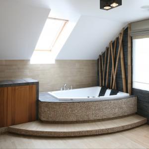 Utrzymaną w stylistyce SPA łazienkę zdobią naturalne materiały - kamień i drewno. Ulokowana pod skosami dwuosobowa wanna została obudowana  przypominającymi mozaikę otoczakami. Ścianę przy zagłówkach zdobią oryginalne bambusy. Projekt Karolina Łuczyńska. Fot. Bartosz Jarosz.