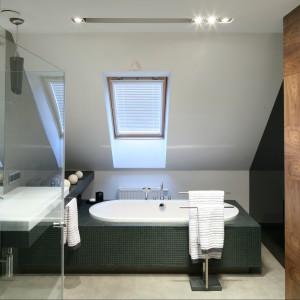 Utrzymaną w biało-czarnej stylistyce łazienkę ocieplają drewniane elementy. Obudowana mozaiką wanna została lekko odsunięta od ściany ze skosem. Dzięki temu zabiegowi powstało dodatkowe miejsce na zamontowanie kaloryfera. Projekt Luiza Jodłowska. Fot. Bartosz Jarosz.