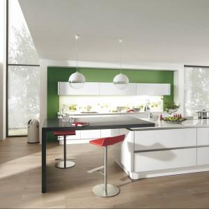 Meble z kolekcji Vitrus firmy Wellmann. Białe fronty w wysokim połysku doskonale pasują do zielonej ściany. Na wyspie znajduje się strefa gotowania i przygotowywania posiłków oraz przechowywania. Przedłużeniem wyspy jest wygodny stolik.