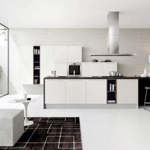 Meble z kolekcji Cromatika firmy Doimo Cucine. Białe fronty mebli doskonale prezentują się na tle ceglanej ściany. Wyspa, zajmująca centralne miejsce w kuchni, jest funkcjonalnym centrum dowodzenia. Jest również na tyle duża, że może przy niej wspólnie pracować nawet kilka osób.
