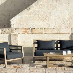Sofę i fotel z kolekcji mebli wypoczynkowych Raw marki Ethimo uzupełnia drewniany stolik kawowy. Fot. Ethimo.