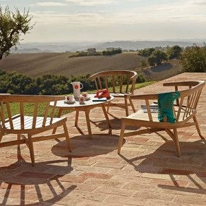 Drewniane krzesła z oparciem z kolekcji Windsor marki Gloster o ciekawych, okrągłych formach. Dodadzą ogrodowi  odrobinę rustykalnej nuty. Fot. Gloster.